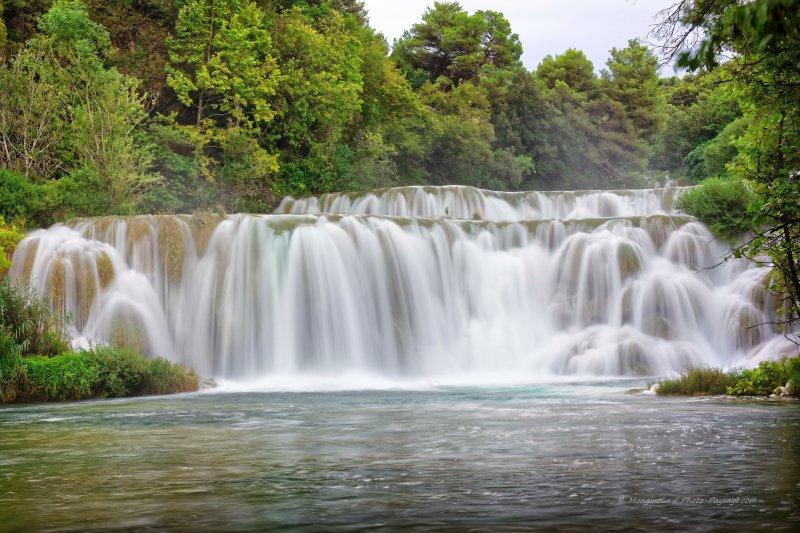 Cascades magnifiques entourées d'arbres, photographiées par un temps couvert en pose longue, dans le parc national de Krka en Croatie.