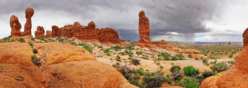 Panorama sur des piliers naturels sculptés par l'érosion dans le parc national d'Arches. Pendant ce temps au loin, un orage se déverse sur ce paysage désertique. Parc national d'Arches. Moab, Utah, USA .