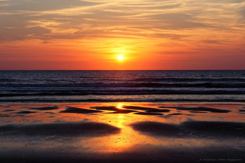 Coucher de soleil, les rayons du soleils se reflètent sur le sable mouillé pendant la marée descendante, au-dessus de l'océan Atlantique, Moliets-et-Maâ, Landes