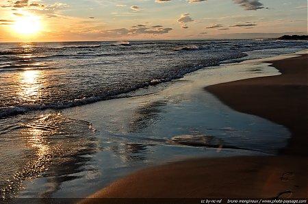 Le soleil couchant se reflète sur le sable humide de la plage Massif dunaire de l'Espiguette Le Grau du Roi / Port Camargue (Gard).